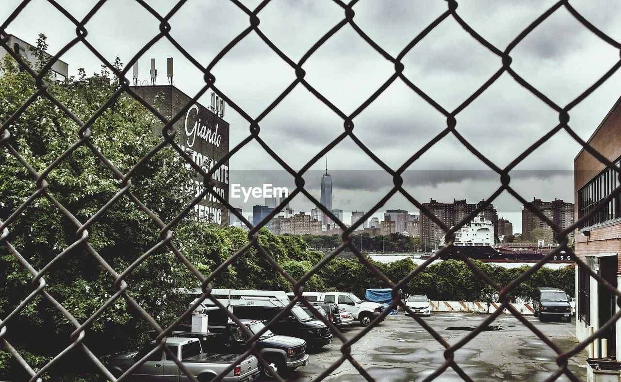 chainlink fence, chainlink, city, architecture, building exterior, metal, protection, built structure, safety, day, no people, outdoors, sky, cityscape, water, nature, close-up