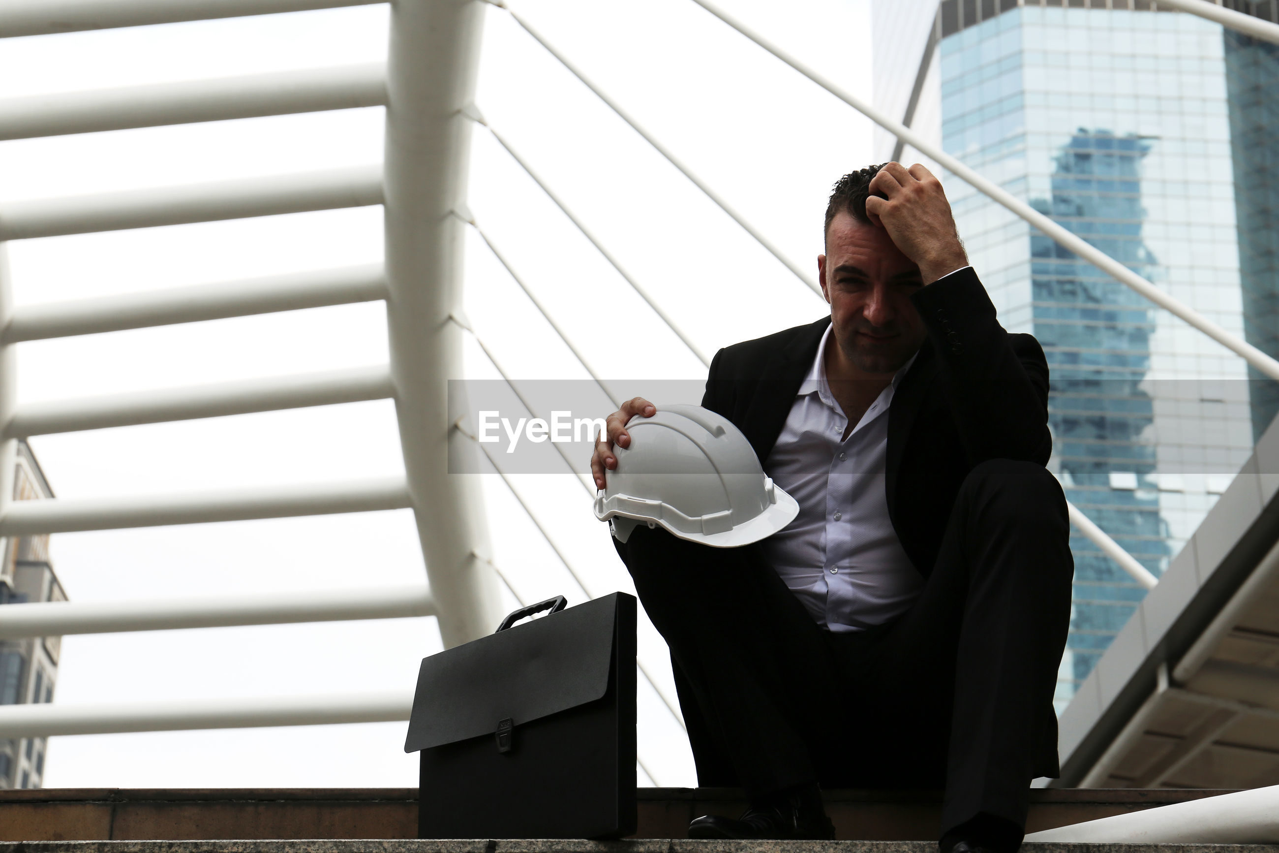 Frustrated businessman sitting against built structure