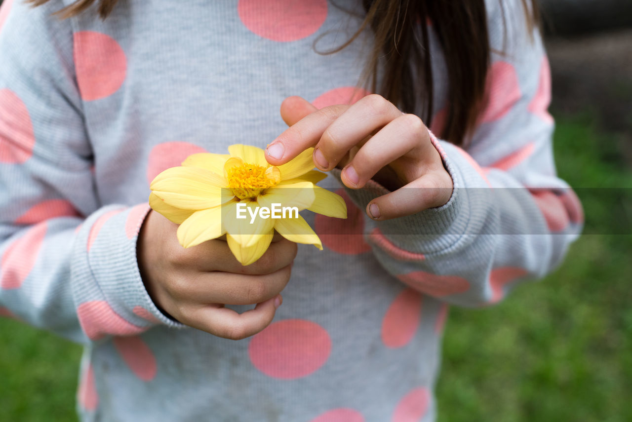 Close-Up Of A Girl Holding Flower