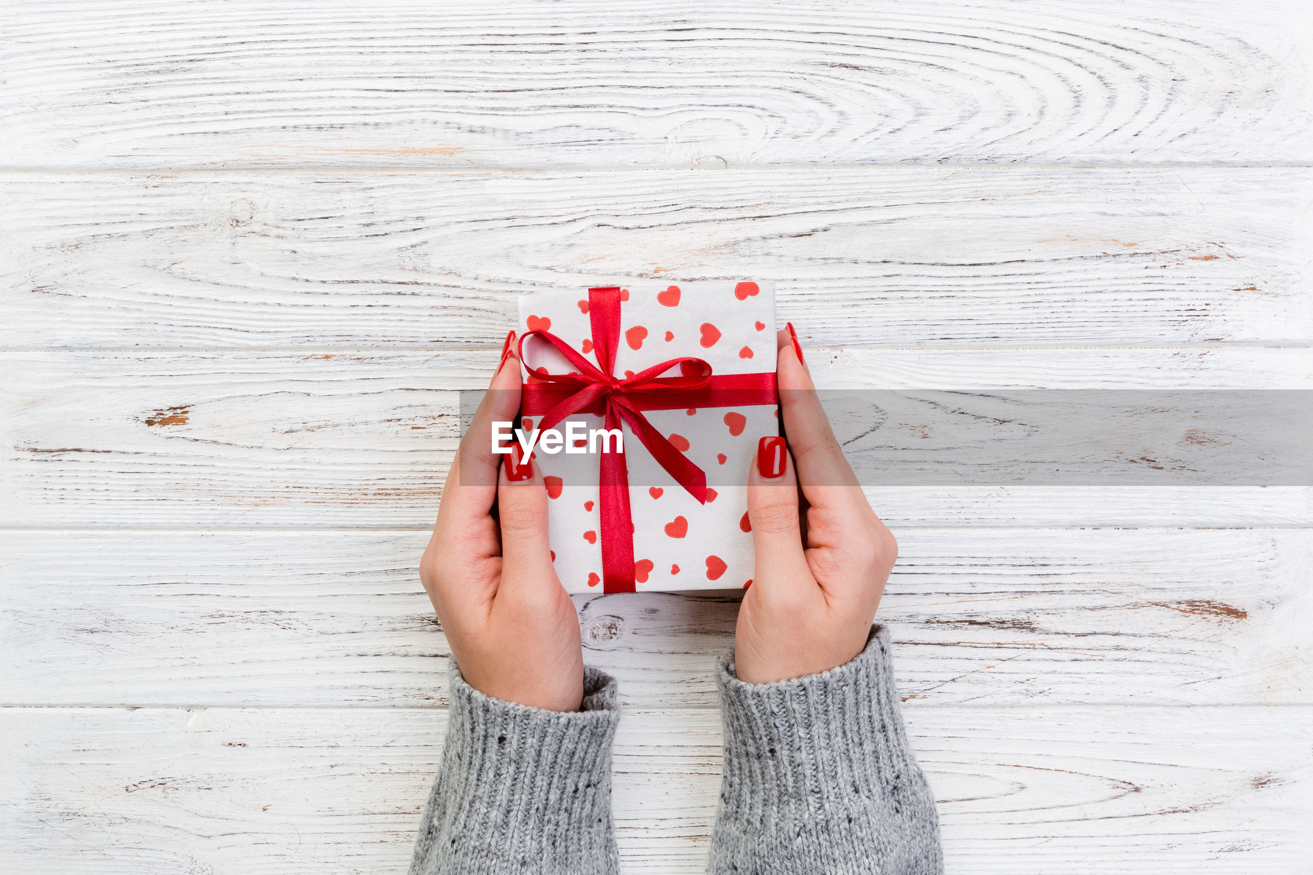 Cropped hands of woman holding gift on table