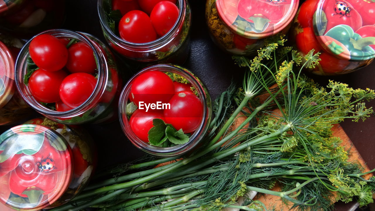 Close-Up Of Tomatoes In Glass Jars By Dill On Table