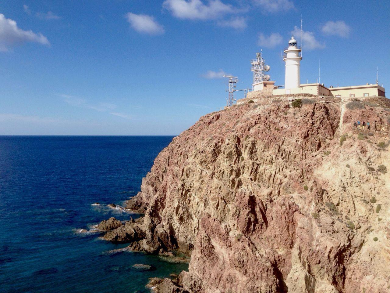 Lighthouse On Mountain By Sea Against Sky