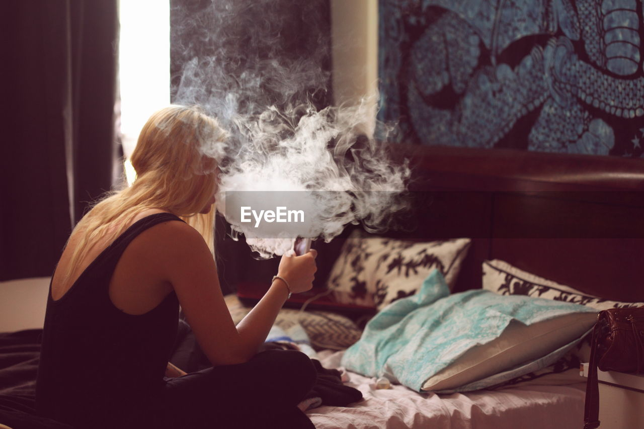 Blond Woman Smoking While Sitting In Bedroom