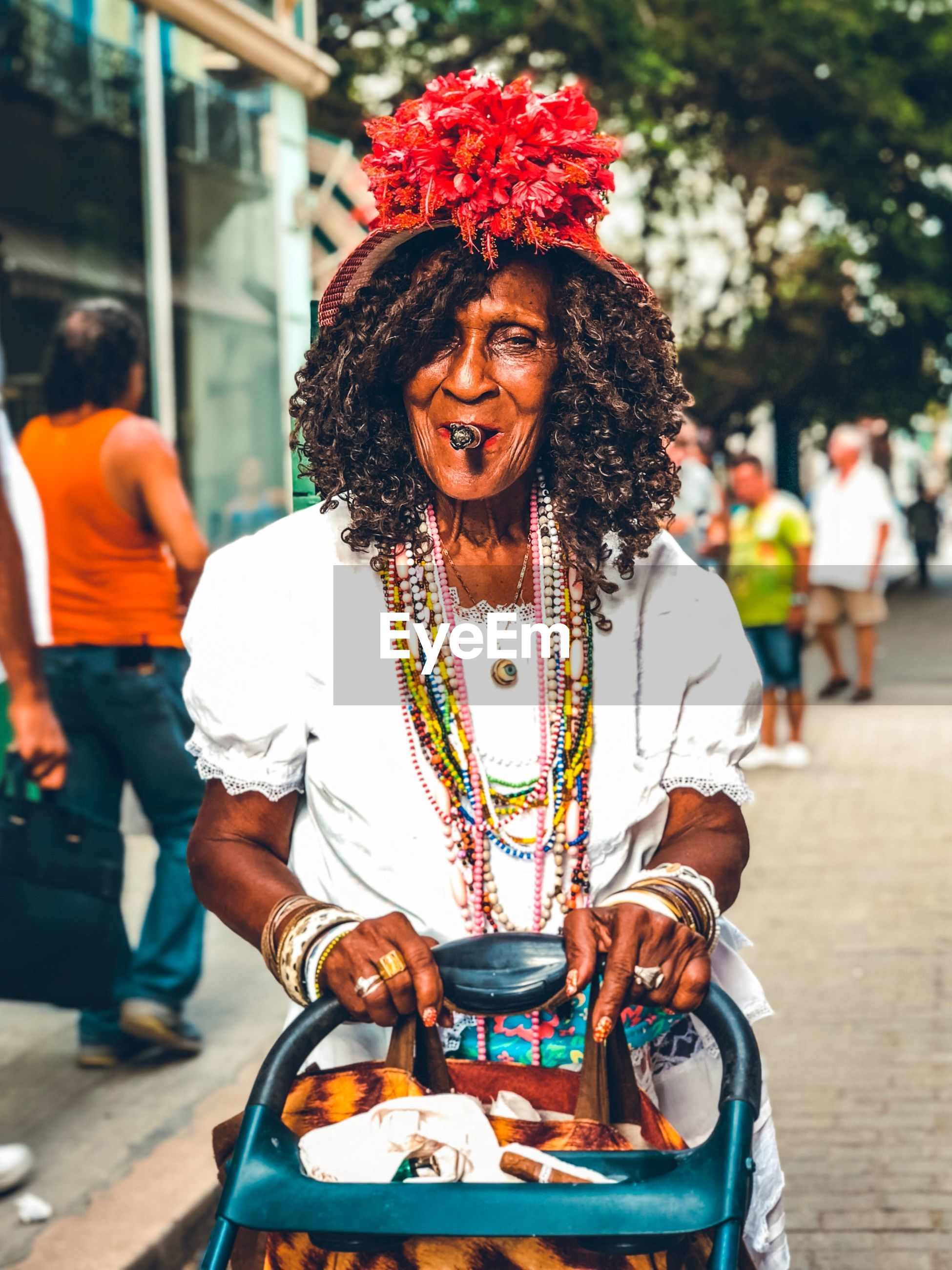 Woman wearing colored necklaces and fancy hat while standing on street in city
