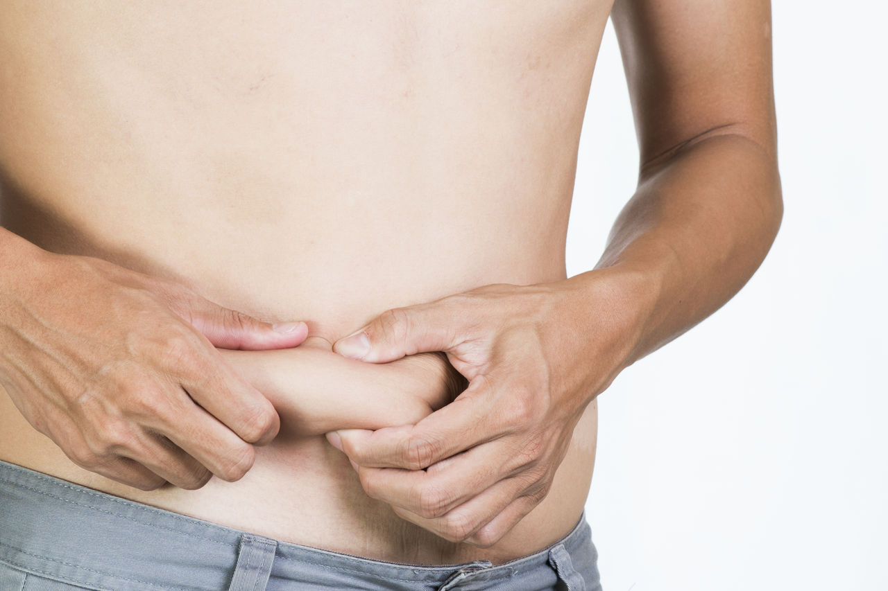 Midsection of overweight shirtless man touching abdomen against white background