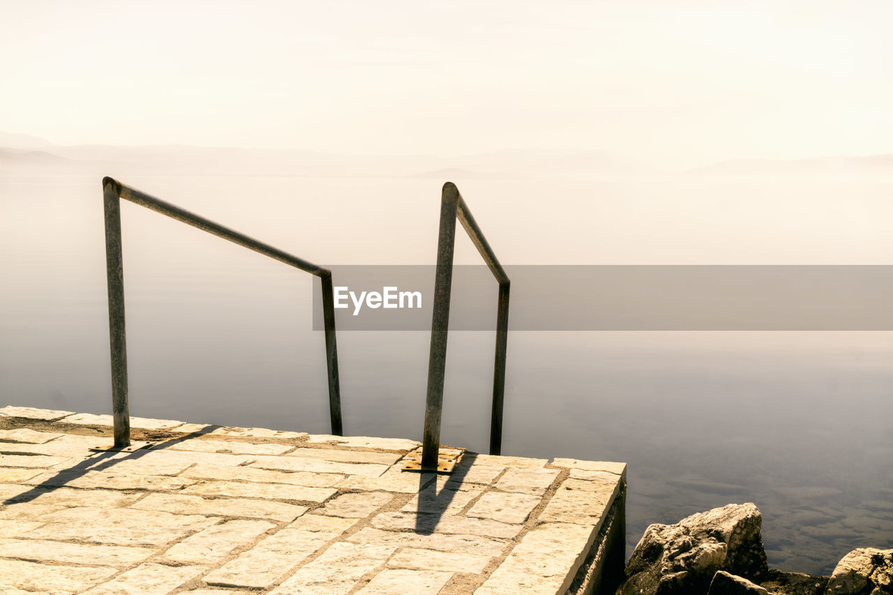 sky, nature, scenics - nature, water, beauty in nature, day, no people, tranquil scene, tranquility, rock, sea, solid, clear sky, rock - object, outdoors, architecture, railing, sunlight