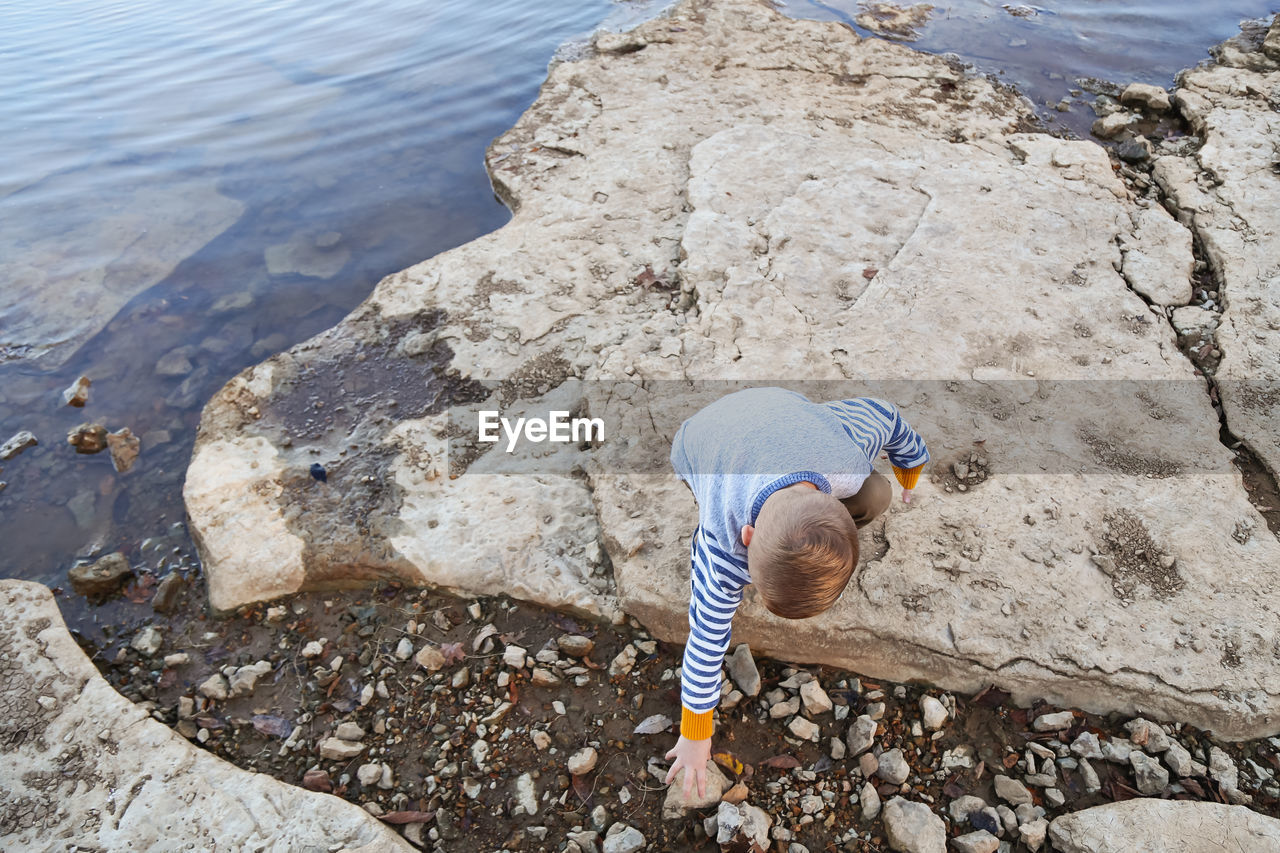 High angle view of boy reaching on rock against sea