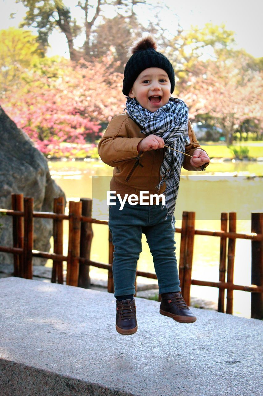 Portrait of cute baby boy jumping on footpath against river