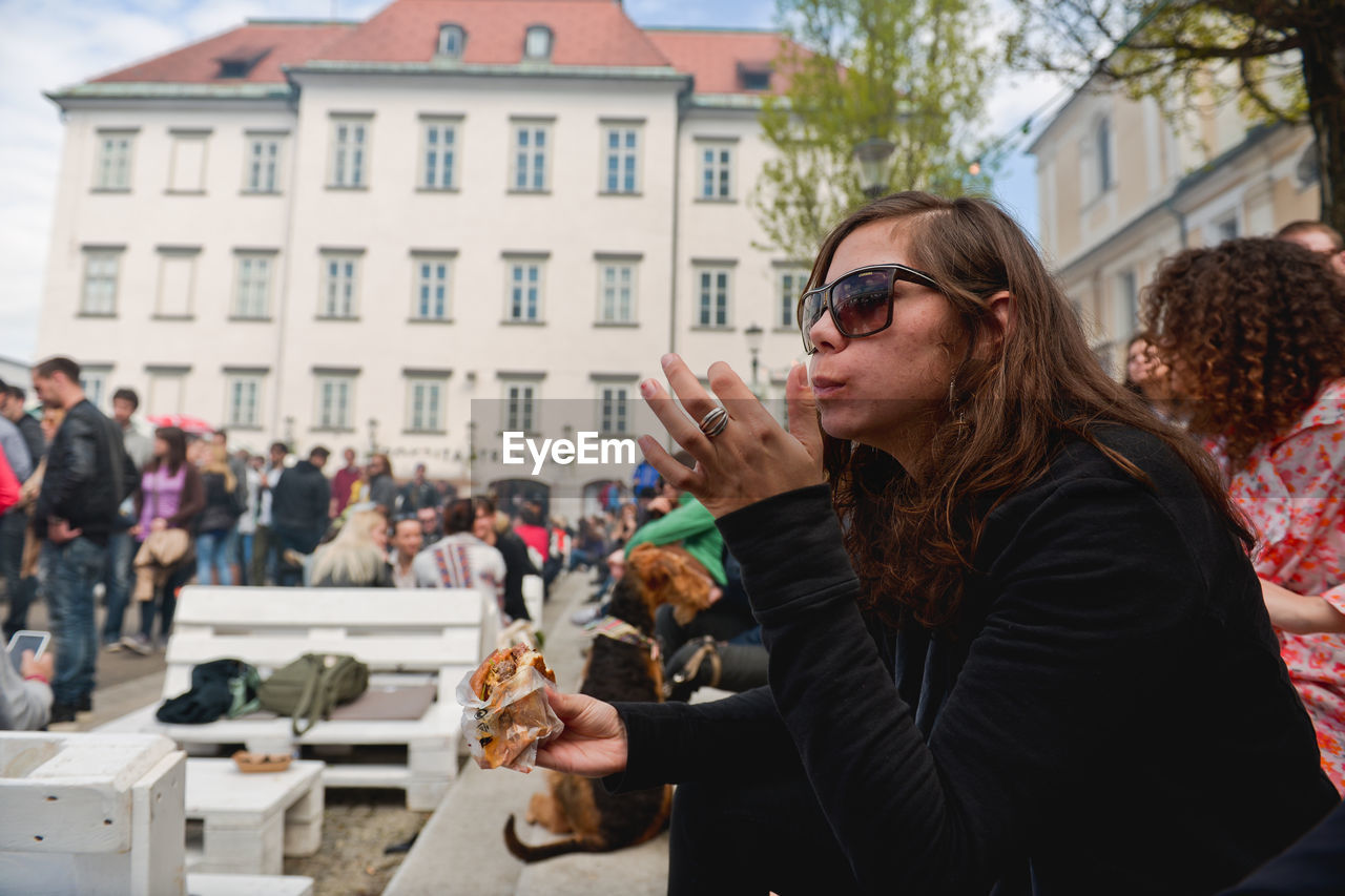 real people, architecture, city, food and drink, lifestyles, building exterior, leisure activity, glasses, holding, people, adult, women, drink, built structure, young adult, day, sunglasses, cup, incidental people, outdoors, drinking