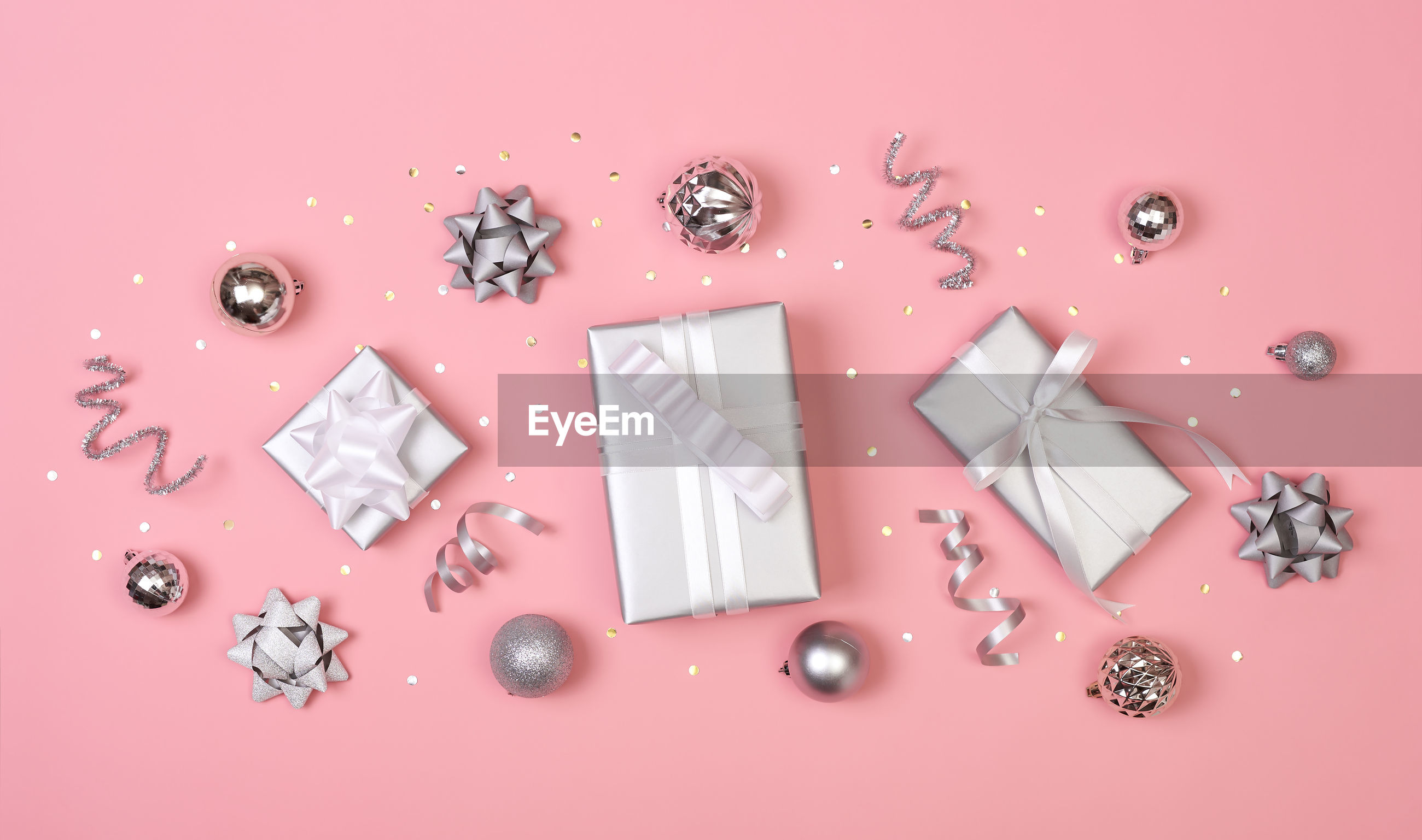 High angle view of gifts and decoration over pink background