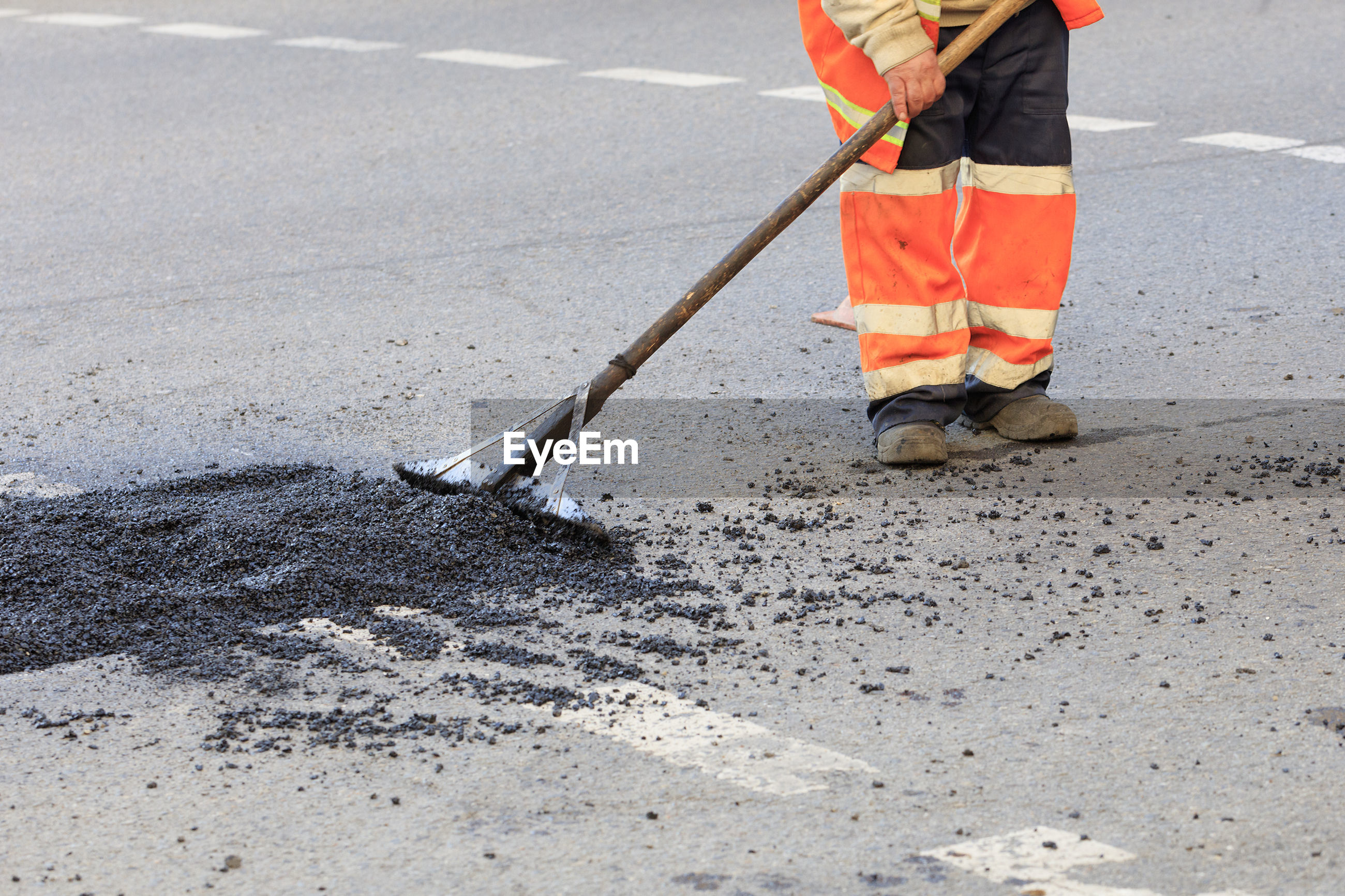 Low section of man working on road at construction site