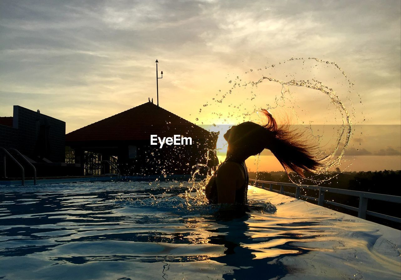 WOMAN WITH SWIMMING POOL AGAINST SKY DURING SUNSET