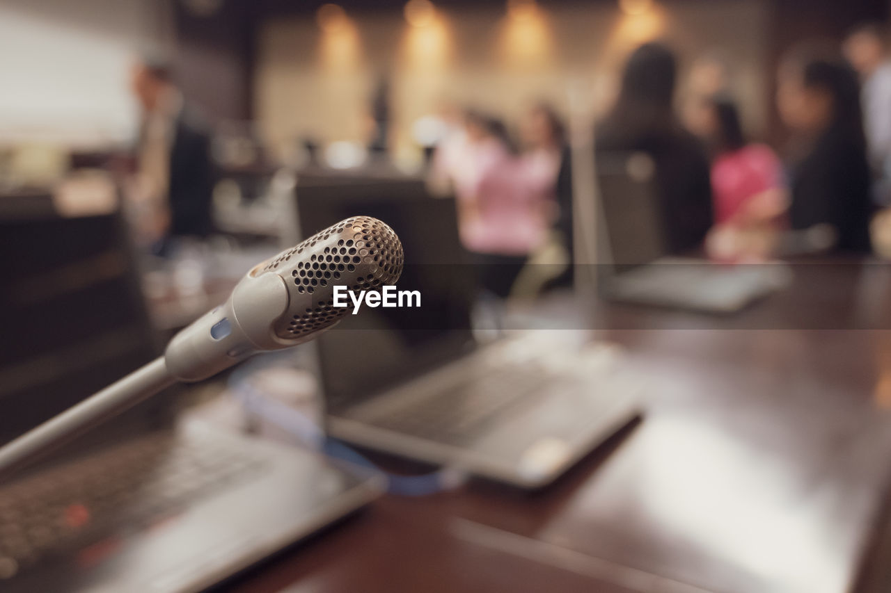 microphone, technology, input device, table, incidental people, communication, indoors, music, focus on foreground, selective focus, connection, close-up, arts culture and entertainment, equipment, adult, women, group of people, still life, audio equipment, talking