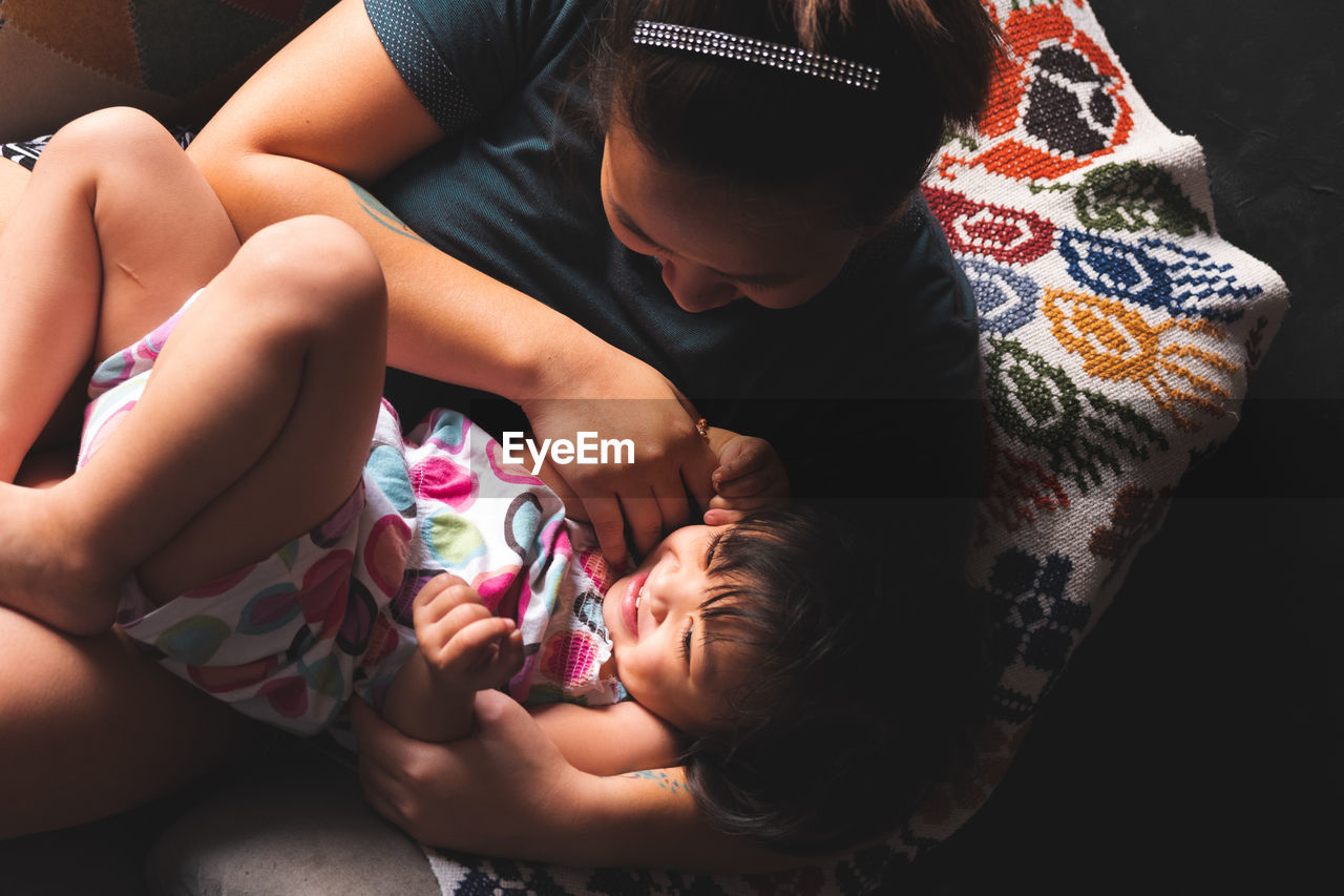 child, childhood, family, real people, bonding, lifestyles, togetherness, women, relaxation, indoors, parent, females, family with one child, innocence, adult, casual clothing, high angle view, love, positive emotion, sister