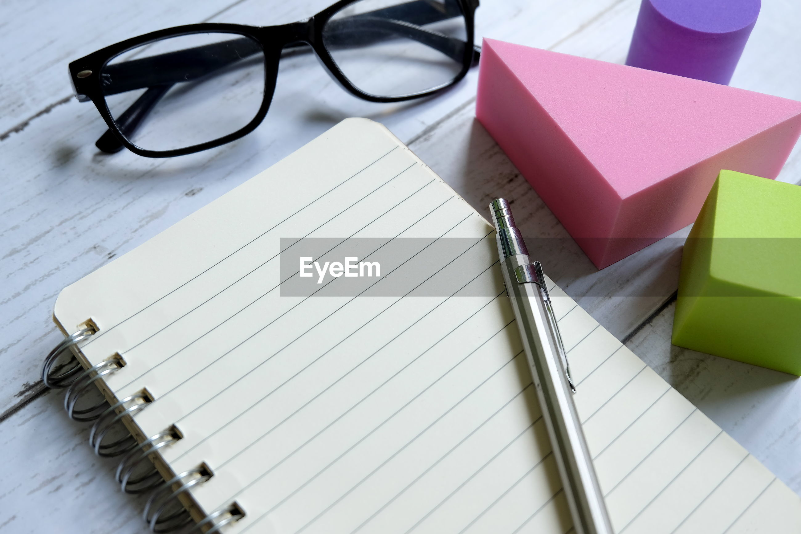 Close-up of book with pen and eyeglasses on table