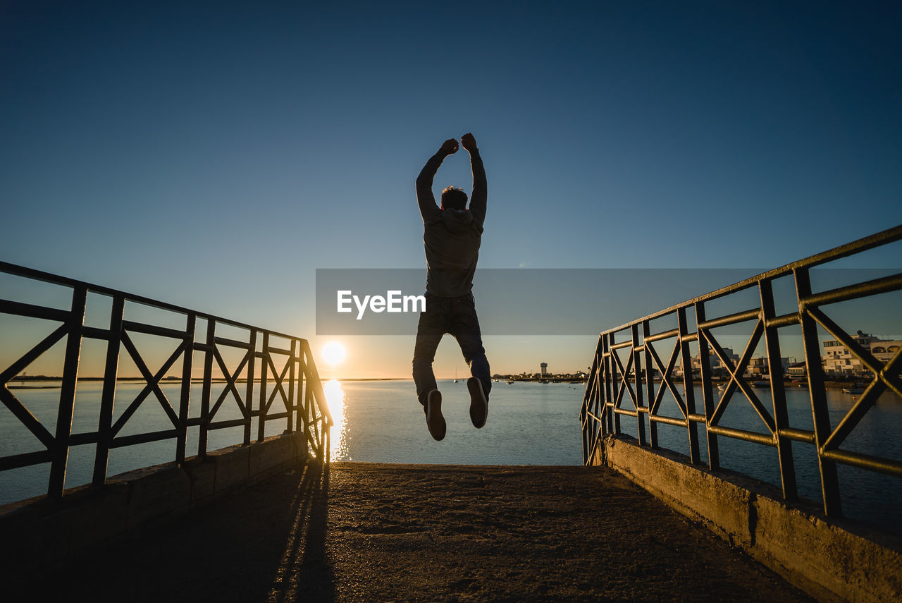 Full Length Of Man Jumping Over Pier At Beach Against Sky During Sunset