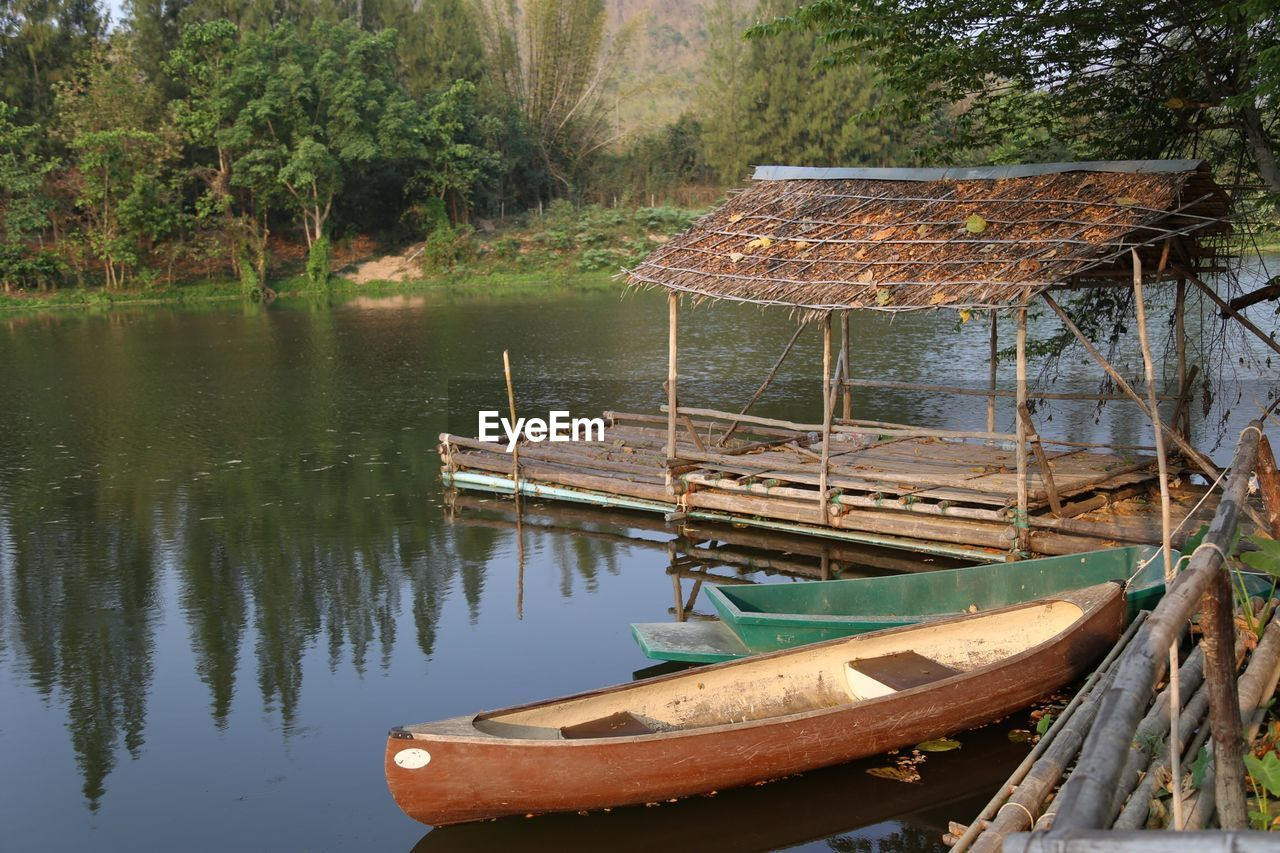 water, nautical vessel, transportation, mode of transportation, moored, nature, tree, lake, day, reflection, no people, wood - material, tranquility, beauty in nature, wooden raft, plant, tranquil scene, outdoors, rowboat