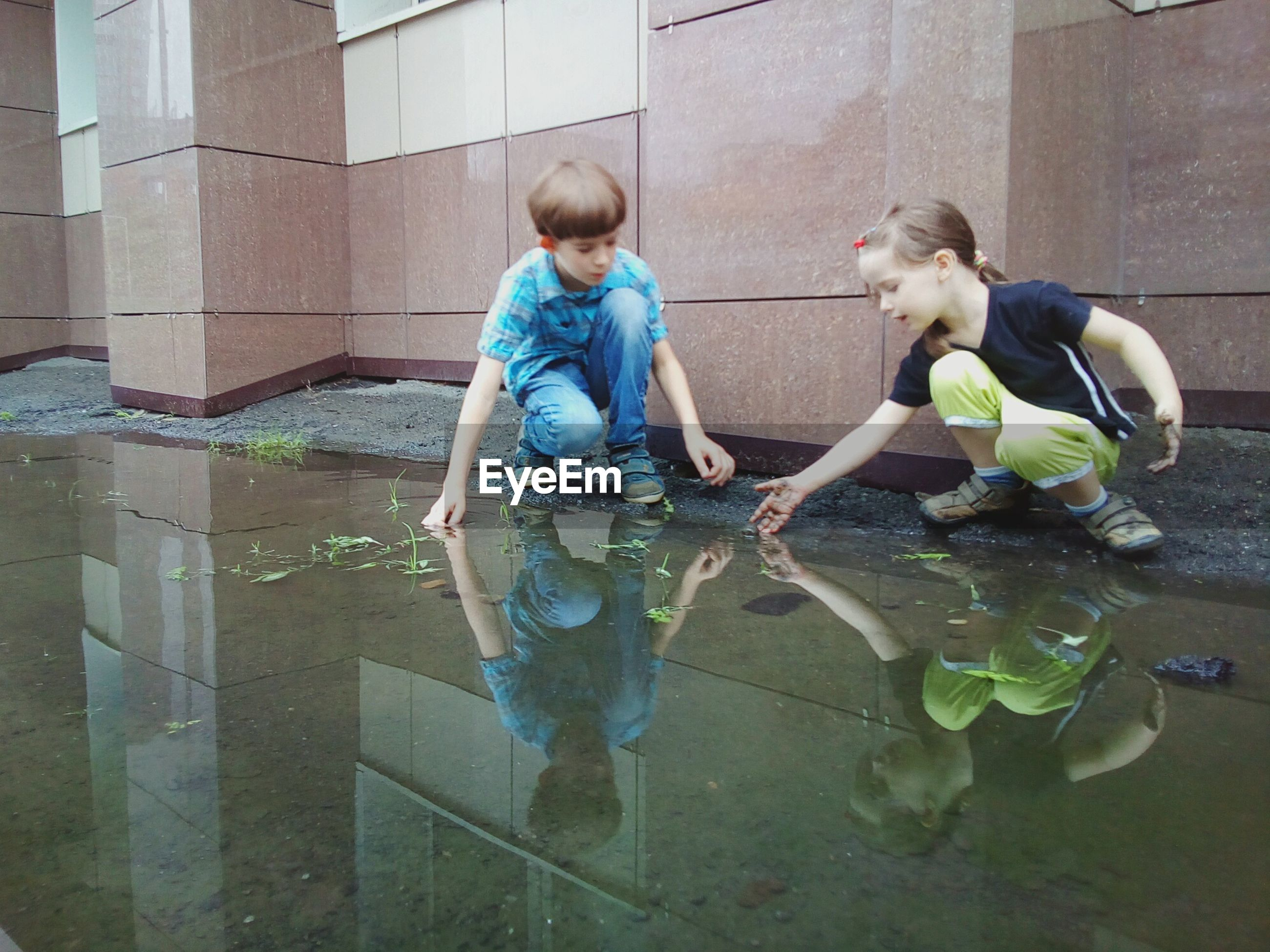 Siblings playing in puddle by building