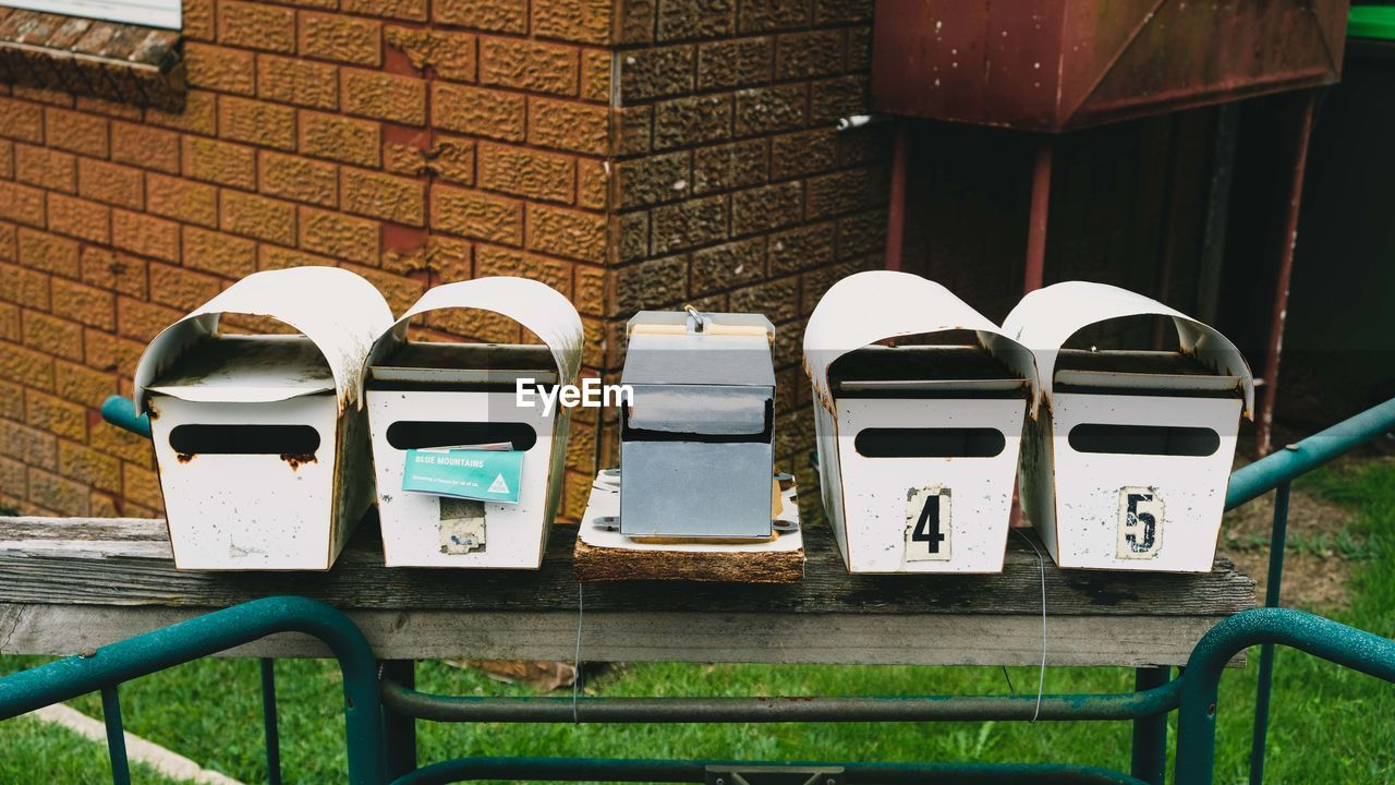 day, mailbox, seat, no people, chair, communication, wall, outdoors, brick, correspondence, nature, side by side, wall - building feature, garbage bin, brick wall, close-up, railing, wood - material, absence, metal