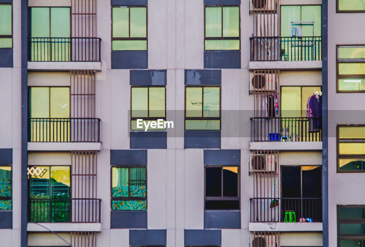 FULL FRAME SHOT OF BUILDING WITH MULTI COLORED WINDOWS