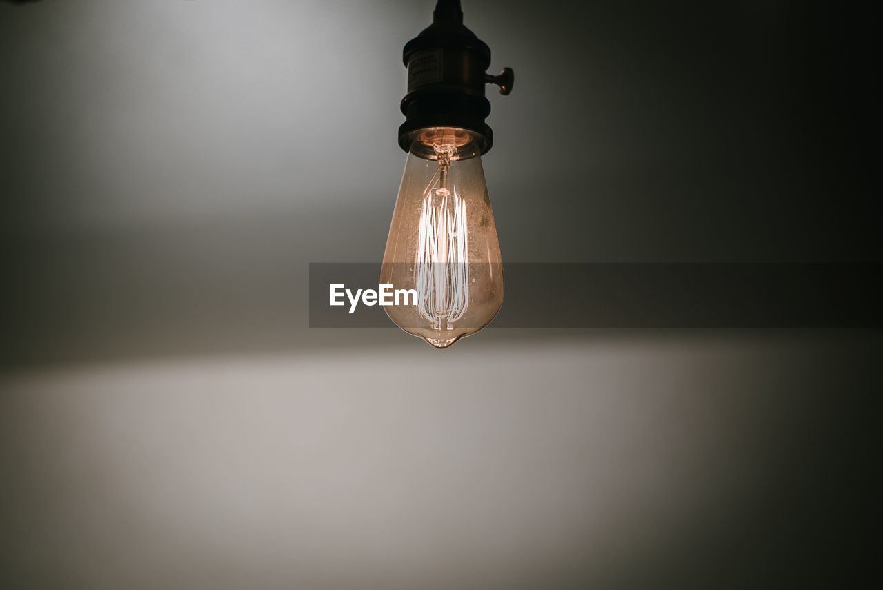 lighting equipment, electricity, illuminated, light bulb, indoors, light, close-up, single object, wall - building feature, no people, electric light, glowing, filament, technology, hanging, glass - material, bulb, copy space, light - natural phenomenon, dark, electric lamp, power supply, ceiling