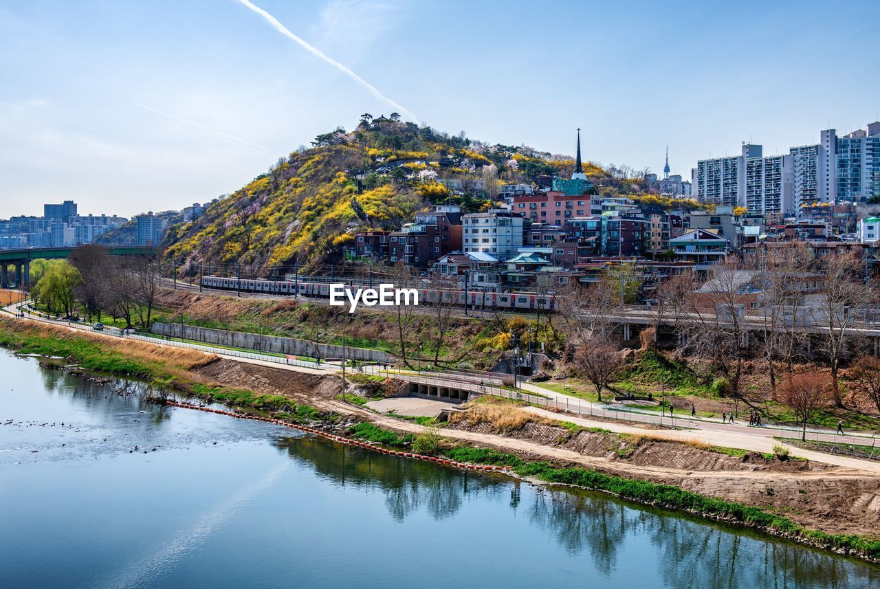 SCENIC VIEW OF RIVER AND BUILDINGS AGAINST SKY