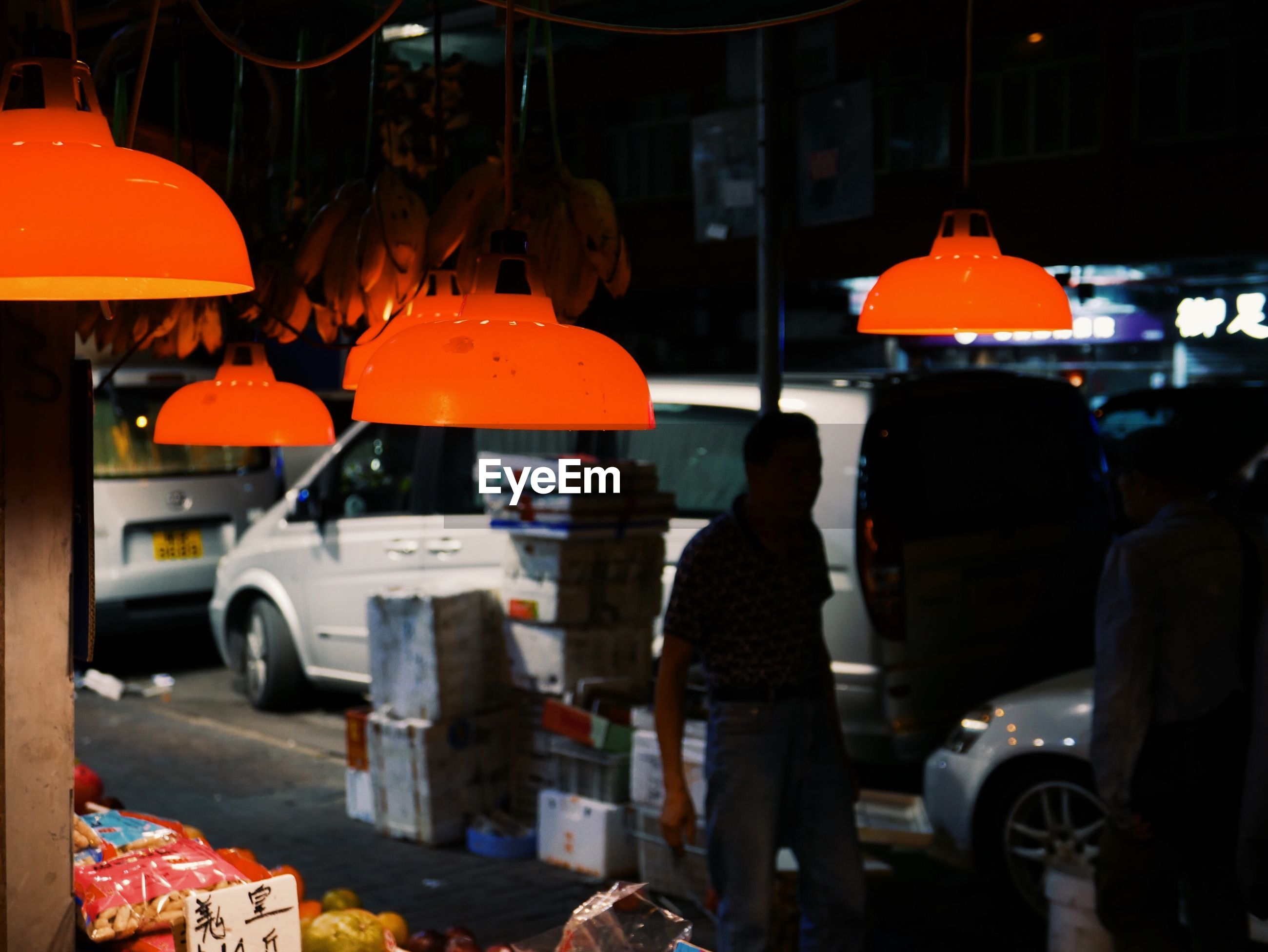 mode of transportation, transportation, motor vehicle, car, city, street, real people, land vehicle, men, orange color, architecture, road, people, group of people, standing, occupation, illuminated, incidental people, city street, focus on foreground