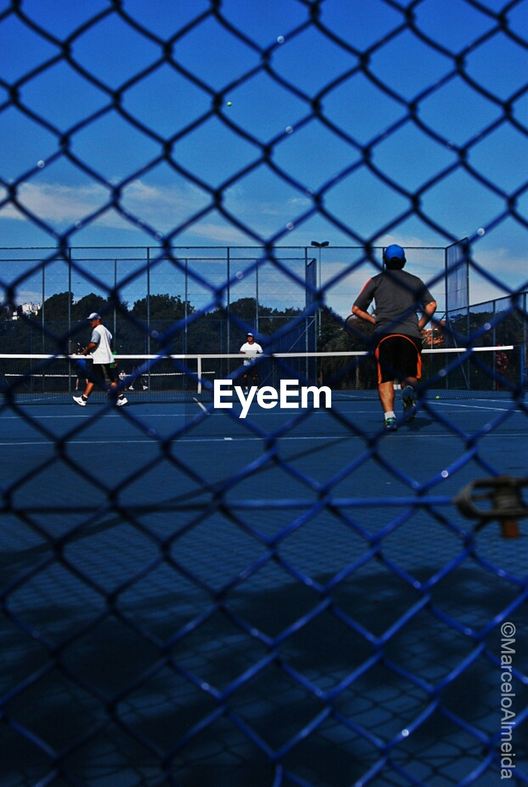 leisure activity, lifestyles, protection, sky, men, chainlink fence, safety, metal, built structure, sport, fence, blue, standing, architecture, boys, childhood, security, city