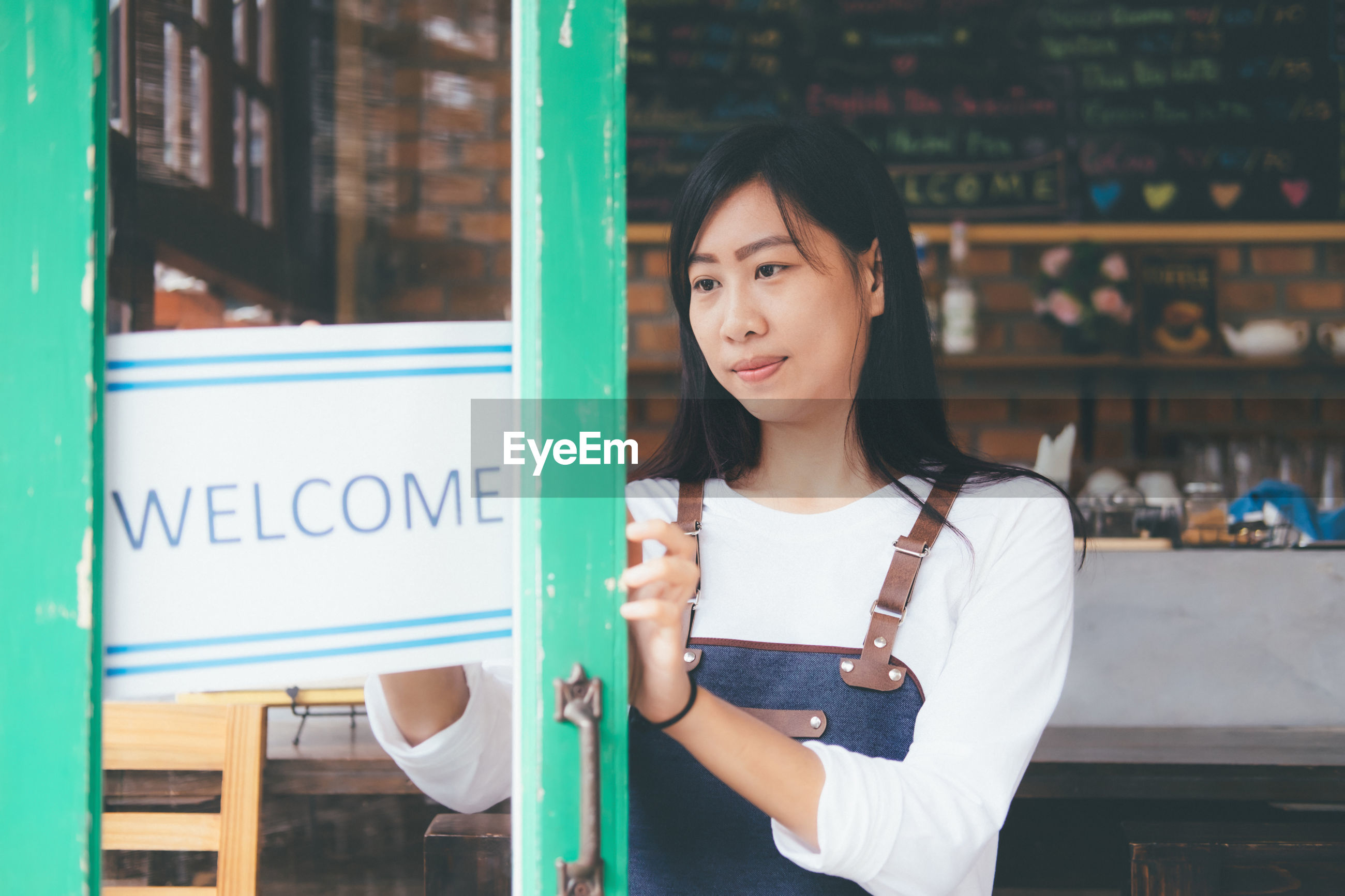 Owner with welcome sign standing in store