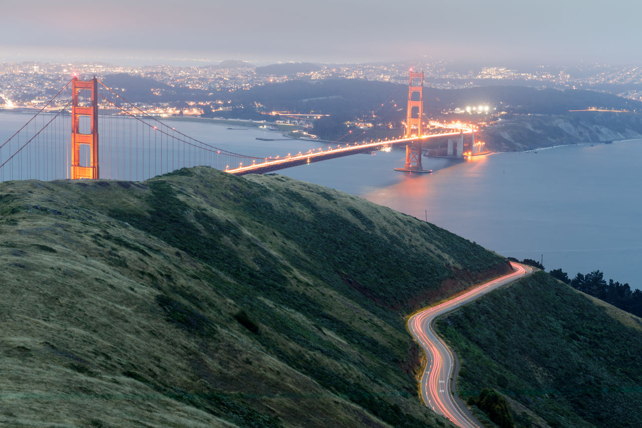 Car light trails and the golden gate bridge glowing at night
