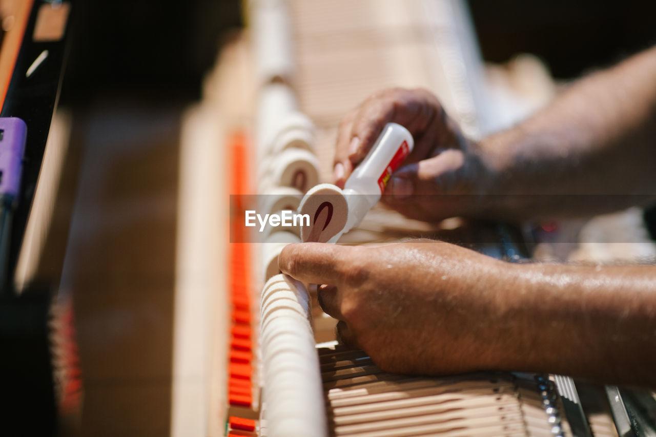 Cropped Hands Of Man Repairing Piano