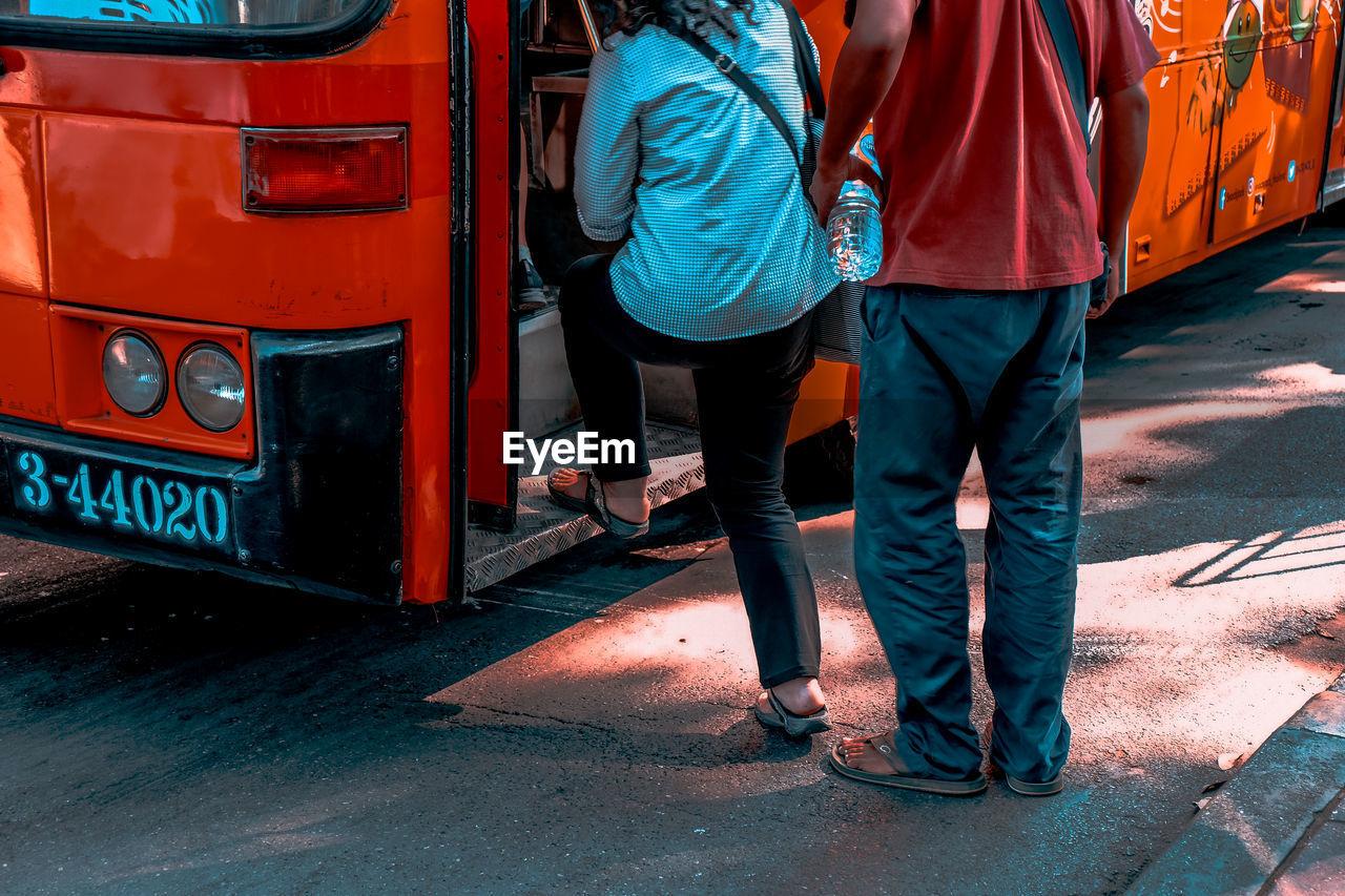 REAR VIEW OF PEOPLE WALKING ON STREET