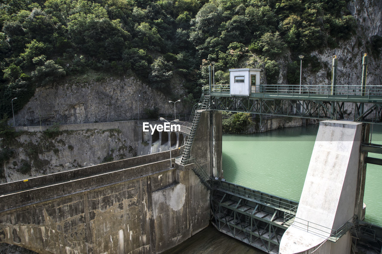 water, built structure, tree, architecture, nature, connection, bridge, plant, day, transportation, river, bridge - man made structure, no people, dam, hydroelectric power, railing, outdoors, fuel and power generation, wall