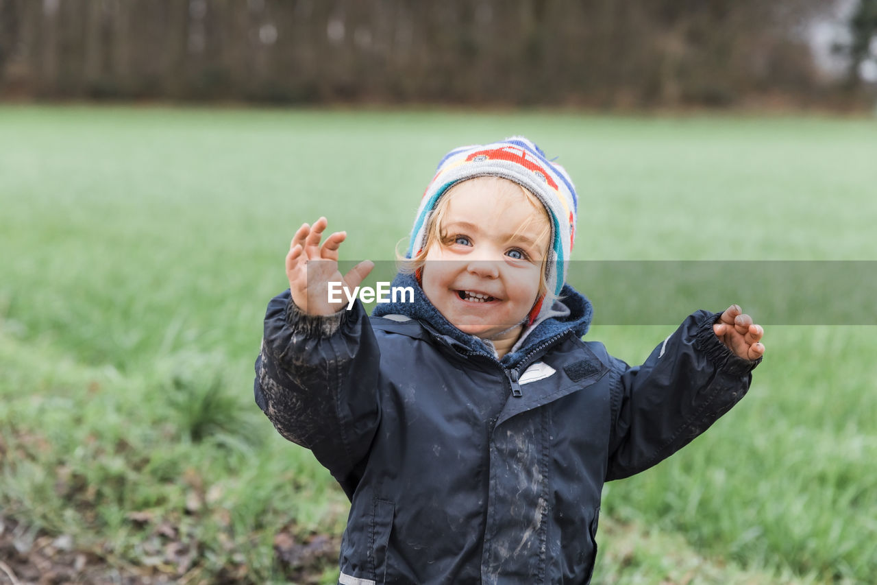 one person, childhood, child, clothing, front view, grass, portrait, day, focus on foreground, land, real people, males, field, nature, innocence, men, emotion, plant, boys, warm clothing, outdoors