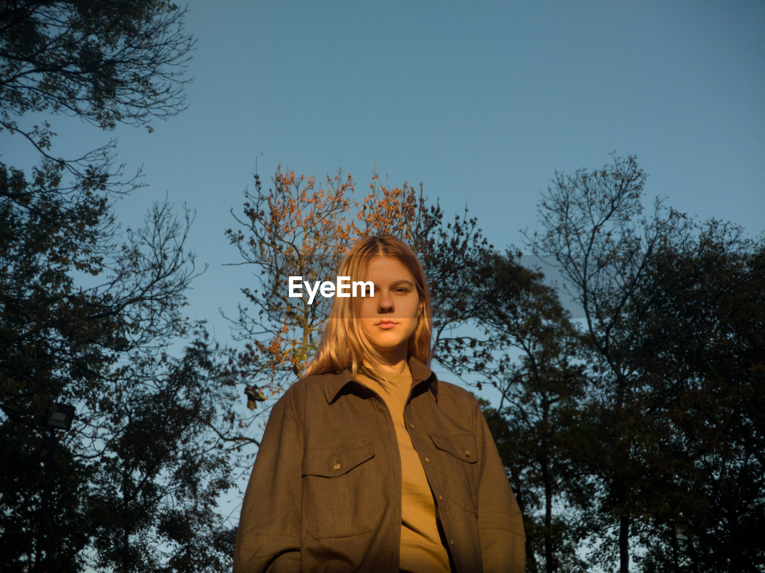 Portrait of smiling woman standing against trees and sky