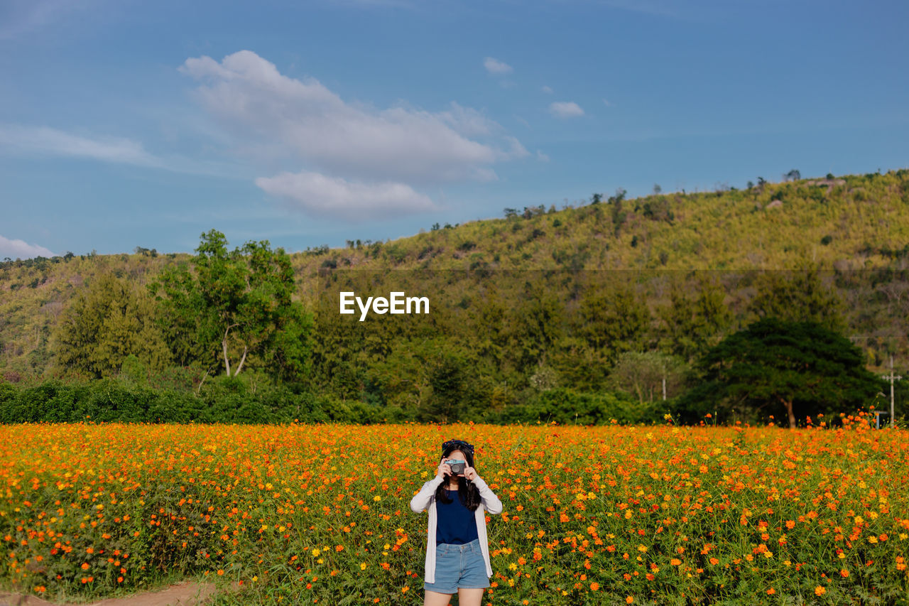 Woman Photographing While Standing On Flower Field Against Sky