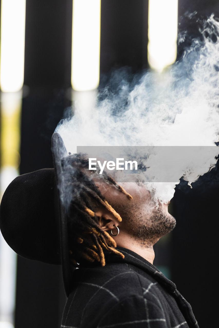 FULL LENGTH PORTRAIT OF MAN SMOKING CIGARETTE ON WOOD