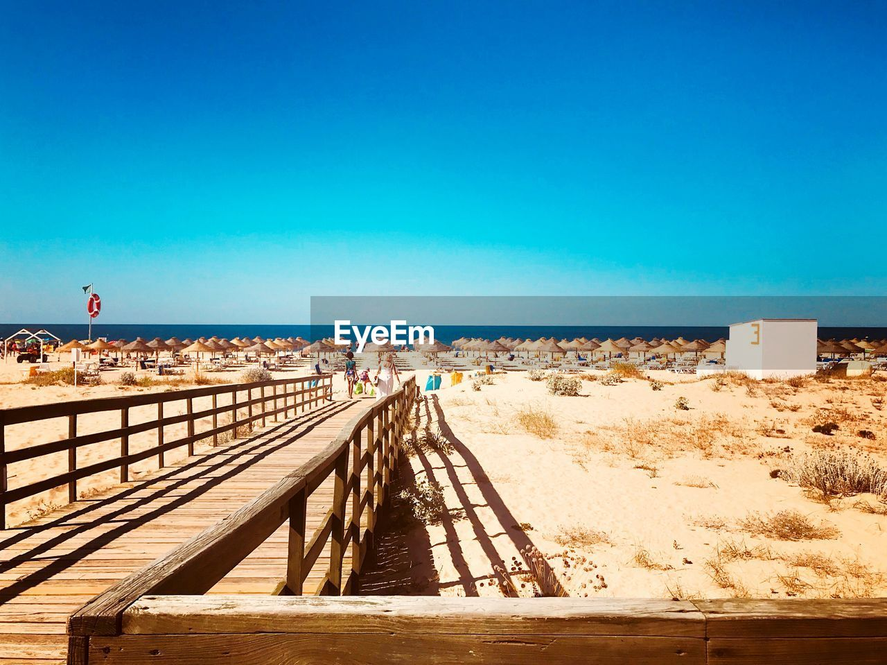 Wooden pier at beach against clear blue sky during sunny day