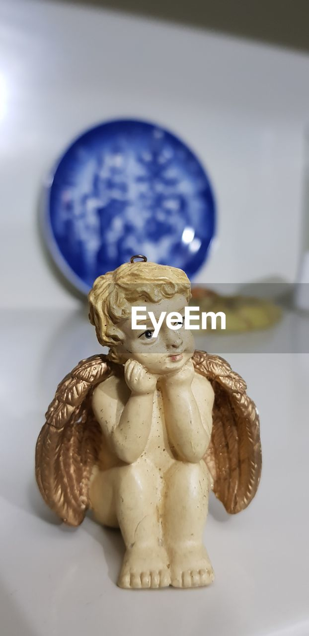 human representation, representation, indoors, figurine, still life, no people, art and craft, table, male likeness, close-up, female likeness, creativity, craft, blue, focus on foreground, sculpture, angel, ceramics, statue, white color