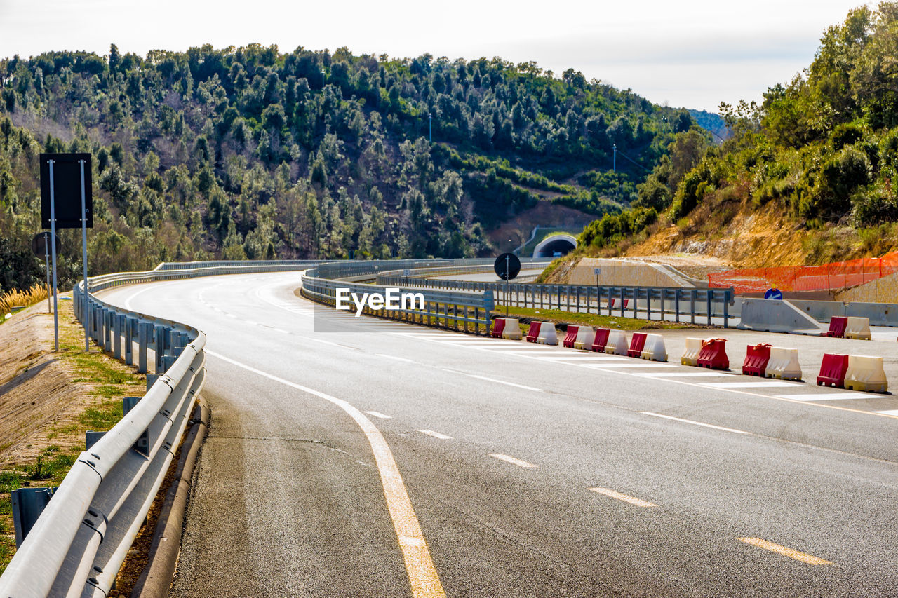 road, transportation, tree, plant, sign, road marking, marking, mode of transportation, nature, day, symbol, no people, mountain, curve, street, direction, motor vehicle, crash barrier, outdoors, the way forward