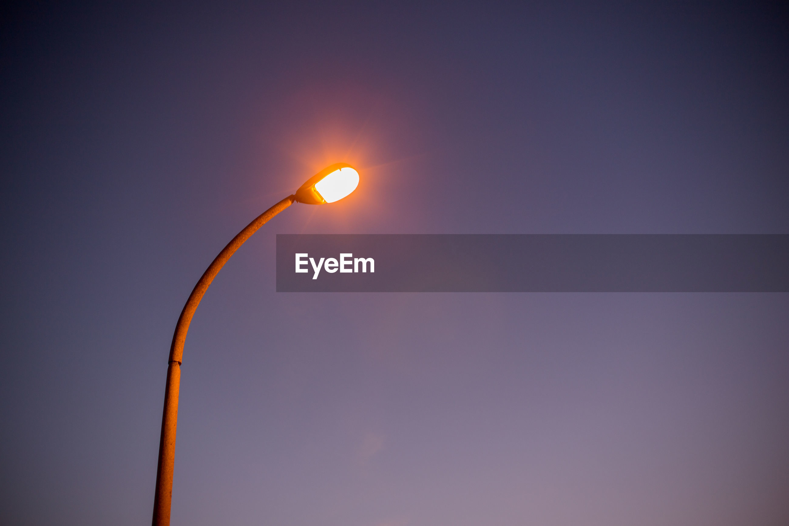 Low angle view of illuminated street light against sky at dusk