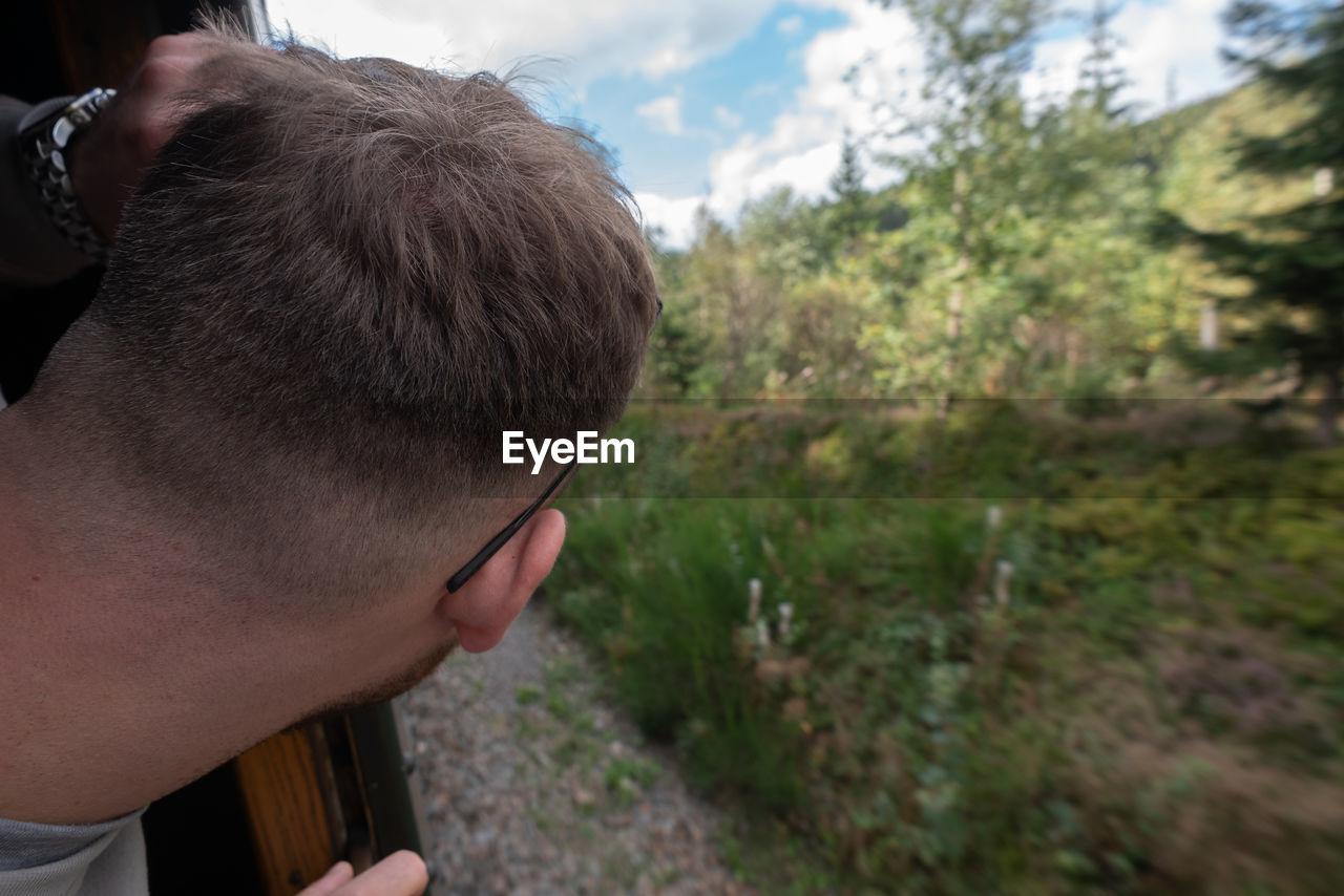 Close-up of man peeking through train window