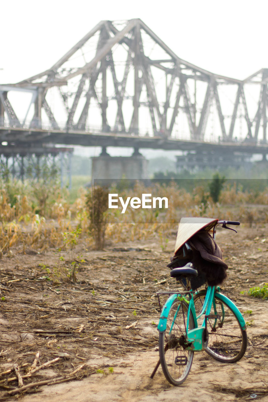 Bicycle With Hat In Rice Field Against Bridge