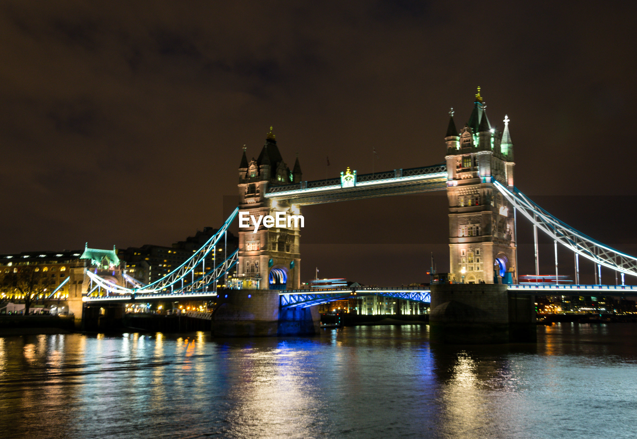 Tower bridge over river at night