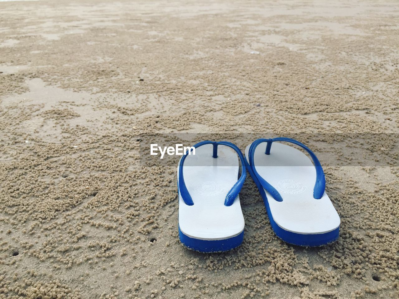 sand, land, blue, beach, pair, shoe, absence, no people, nature, sandal, two objects, flip-flop, still life, personal accessory, close-up, day, tranquility, slipper, outdoors, compatibility