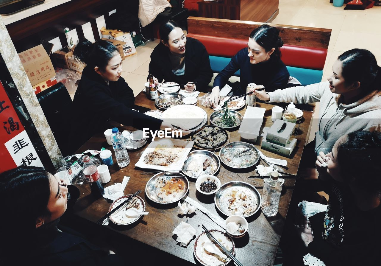 HIGH ANGLE VIEW OF PEOPLE SITTING IN RESTAURANT