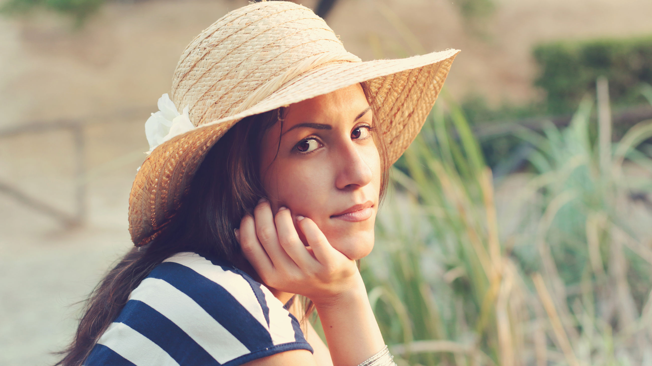 Portrait of young woman wearing hat against plants