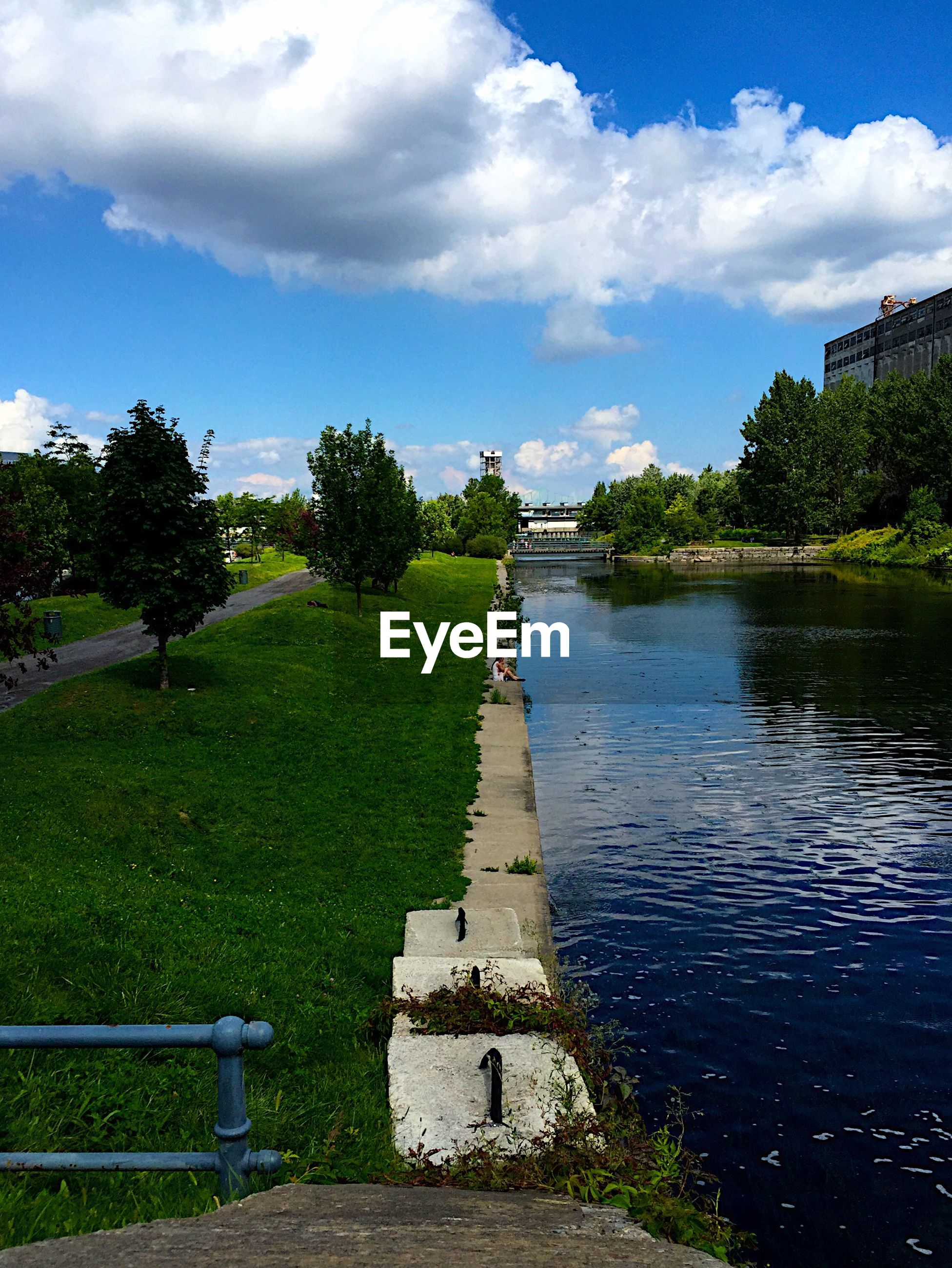 Woman sitting at lachine canal park against sky