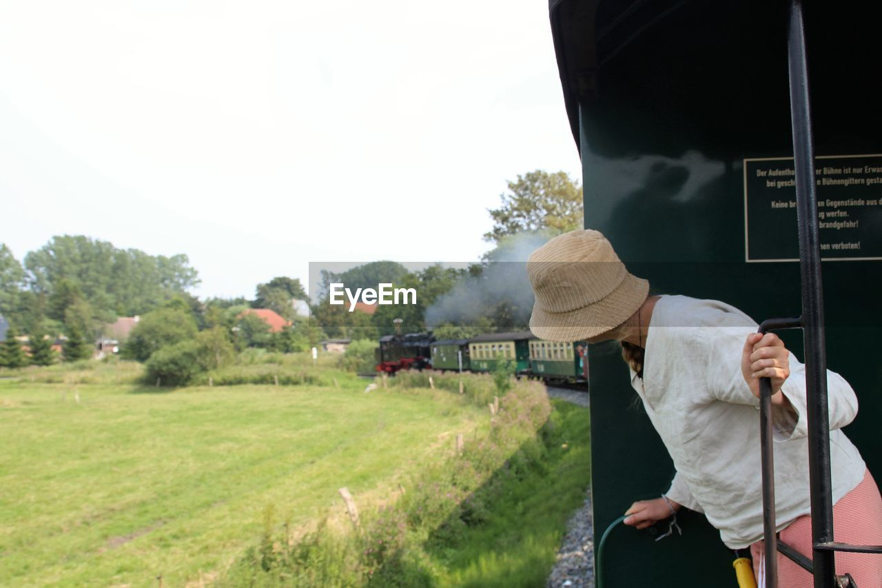 Side View Of Woman Looking Out From Train