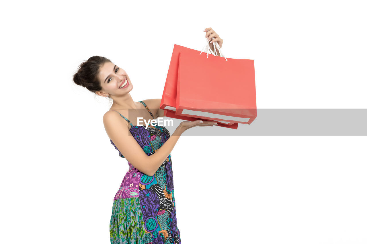 Smiling young woman holding shopping bags while standing against white background